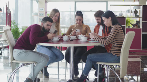 Group of Caucasian friends using smartphones as sitting together in cafe Live Action