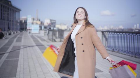 Cheerful chubby woman with shopping bags enjoying sunny autumn day. Joyful Live Action