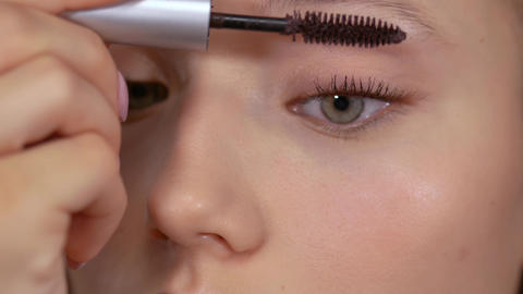 Applying makeup. Young girl looks in the mirror and applies mascara with a brush Live Action