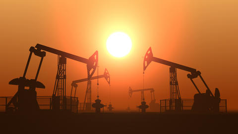 Working oil pump jacks in a desert against sunset extracting crude oil Live Action