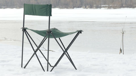 Fishing stool by the river. Winter fishing. River in the background Live Action