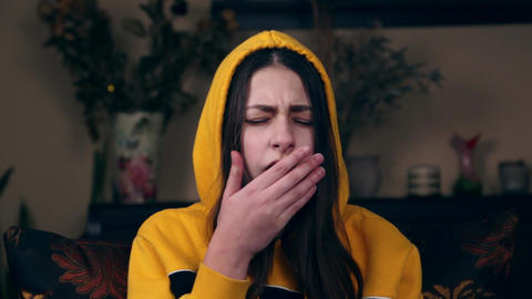 A young girl in a yellow jacket sits on a chair and coughs. Young woman coughs Live Action