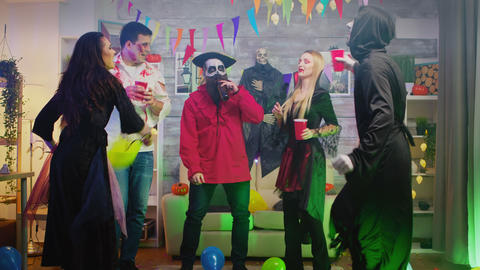 Group of people dancing and having fun at Halloween party in a decorated house Live Action
