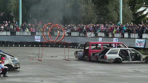 Stuntman on top of car jumps through fire circles, sequence Live Action