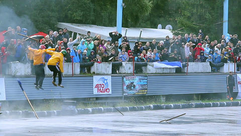 Two stuntmen performing at car stunt show, crowd cheering loudly Live Action