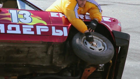 Stunt team changing tire on moving car, two-wheel driving Live Action