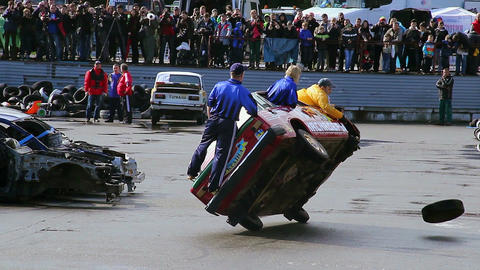 Stunt performers change tire while driving car on two wheels Live Action
