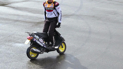 Stuntman riding motorcycle backwards at extreme stunt show Live Action