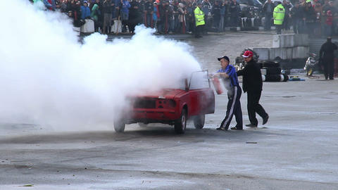 Viewers watching senior man extinguish stunt car fire, sequence Footage