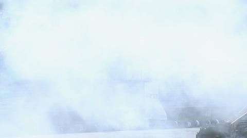 Dense smoke hovering above people at extreme car stunt show Live Action
