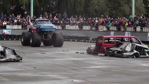 Huge Bigfoot monster truck running over wrecked cars, crashing Live Action