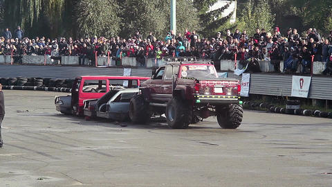 Two Bigfoot trucks destroying old cars at show, huge wheels Live Action