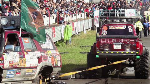 Two Bigfoot monster trucks showing off at extreme stunt show Live Action