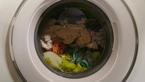 Wet clothes turning in washing machine, view through front glass Footage