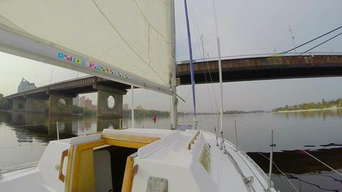Yacht sailing under river city bridge, cityscape, pollution, POV Footage