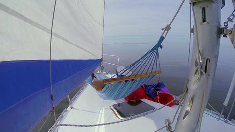 Person relaxing in hammock on sailing yacht, holiday, vacation Footage