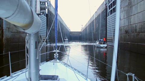 Boat sailing in narrow channel, ready to pass through lock Footage