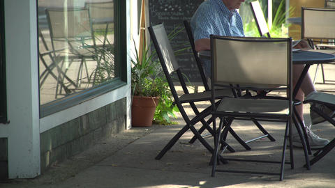 An older man sitting at a street side cafe Footage