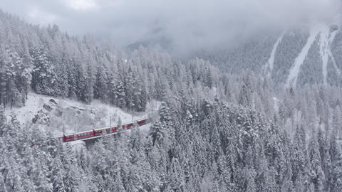 Aerial video of famous train of red color Glacier Express at winter, The train Live Action