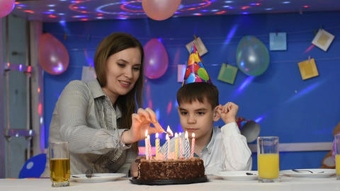 Mom with a child light candles on a birthday cake Live Action