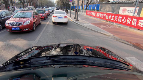 Front view car vehicle driving on downtown city road during day. Beijing, China Live Action
