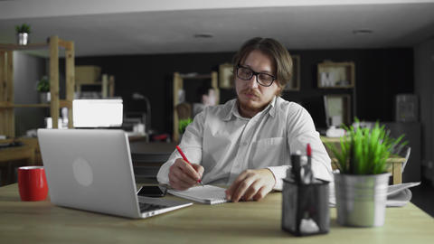 Businessman is working in office writing sitting at desk alone Live Action