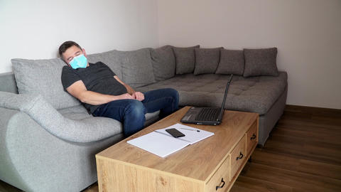 Businessman in medical mask is tired of work and sleeps at the workplace Live Action