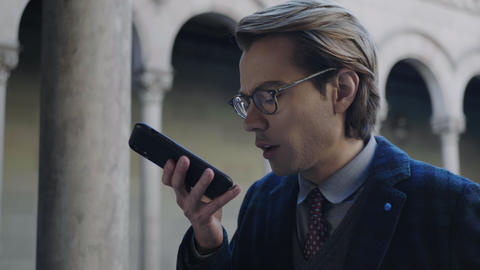 Student recording voice message on cellphone. Man using mobile phone outdoors Live Action