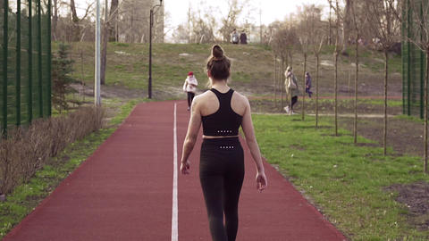 Young woman runner jogging on running track in the park. Activity, person Live Action