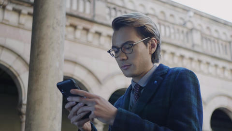 Student using smartphone. Smiling businessman browsing internet outdoors Live Action