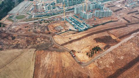 Construction cranes build apartment panel buildings dump trucks carry sand Live Action