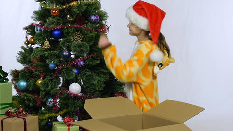 Joyful happy girl takes off balls from a New Year tree and puts in a box Live Action