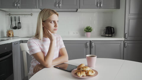 Sad woman using tablet device while having breakfast on her kitchen Live Action