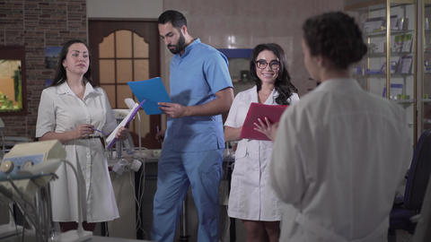 Portrait of positive multi-ethnic dentistry students clapping to young brunette Live Action