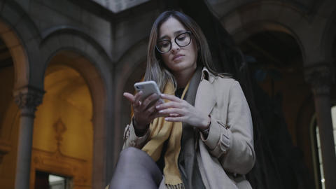 Student reading bad news on phone. Businesswoman working on cellphone outside Live Action