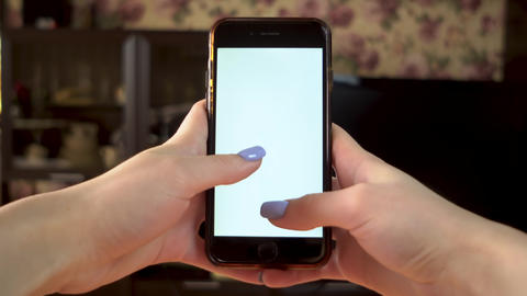 The woman uses the phone. Hands is typing on smartphone with green screen Live Action
