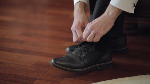 Groom putting his wedding shoes on wedding day. Hands of…, Live Action