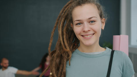 Portrait of pretty young lady with dreadlocks holding yoga mat in gym smiling Live Action