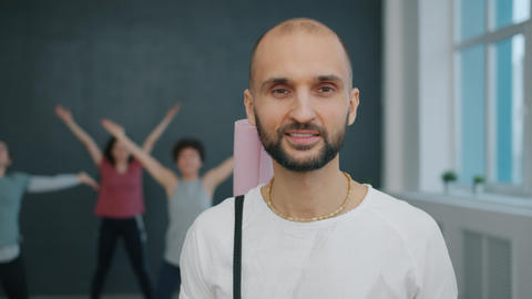 Portrait of attractive guy yoga student smiling in studio holding mat looking at Live Action