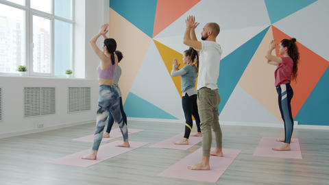 Slow motion of youth doing yoga in gym on mats then making namaste gesture Live Action