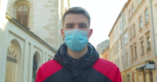 Young student man wearing protective mask on street.Concept of health and safety Live Action