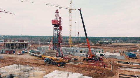 Machinery is building apartment residential area. Red cranes for building an Live Action