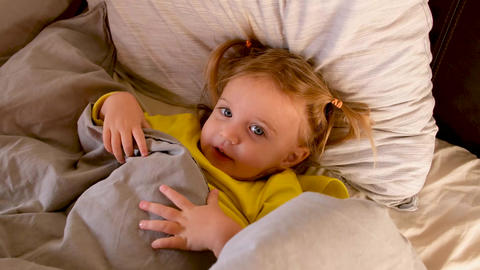 Calm small relaxed girl in bed before sleeping Live Action