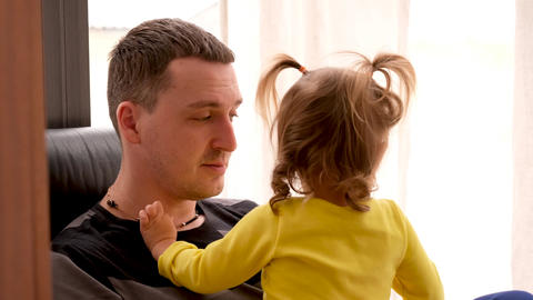 Calm adult father with small daughter spending time together at home Live Action