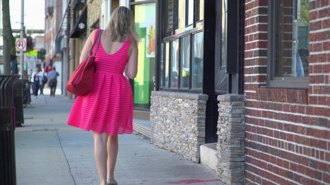 Woman in a bright pink dress walking down a sidewalk Footage