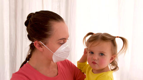 Woman in protective mask with sad ill daughter in modern clinic Live Action