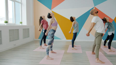 Slow motion of young guy and girls practising yoga in studio bending forward Live Action