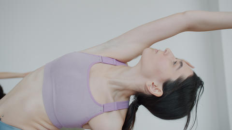 Beautiful young brunette exercising in yoga studio with group of people Live Action