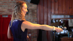 Woman pointing mic at audience to share story Live Action