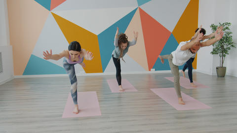 Slow motion of youth exercising in yoga studio doing balancing asanas on mats Live Action